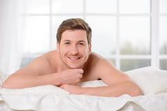 Smiling young man lays awake in bed Stock Photos