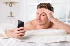 Guy checks his social networks after awakening - stock photo