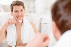 Young man is about to brush his teeth Stock Photos