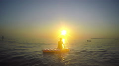 Beautiful young woman relaxing on a yellow inflatable mattress on sea sunset Stock Footage