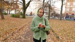 Young woman walks while using smartphone, move through autumn park. Stock Footage