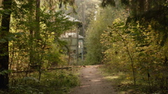 Walkway to the deserted house in the forest. Autumn daytime. Smooth dolly shot. Stock Footage