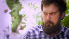 Portrait of a bearded man showing fear, paranoia, and anxiety as a man walks by - stock footage