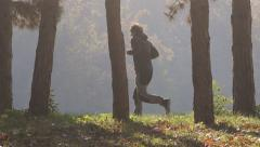 Jogging man running through the park Stock Footage