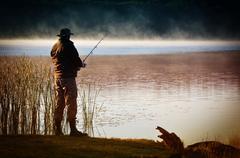 Lone fisherman catches fish - stock photo
