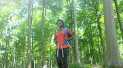 4K Attractive African American woman hiking on her own in the woods - stock footage