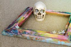 Tiny skulls with colorful wooden frame and flower Stock Photos