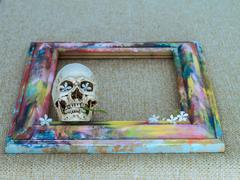 Stock Photo of Tiny skulls with colorful wooden frame and flower
