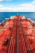 Crude oil carrier with pipeline in open sea. - stock photo