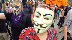 An angry protester from the group Anonymous yells loudly Stock Footage