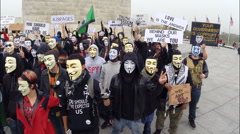Stock Video Footage of Protesters from the group Anonymous pose for a photo before marching.