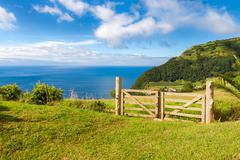 Fields and fence over Atlantic Ocean in Sao Miguel, Azores Islands Stock Photos