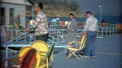 1964: Folks fishing off colorful pier in blue waters lake. - stock footage