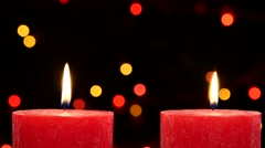 Two red candles with christmas decorations on black, bokeh, light, garland, cam - stock footage