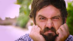 Portrait of a bearded man pulling his hair out in disgust and frustration Stock Footage
