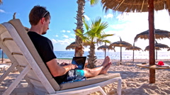 Person at the sand beach typing on laptop Stock Footage