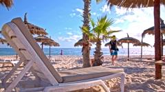 Man leisurely start work on laptop on the beach - stock footage