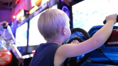 A boy playing a slot machine at an amusement park Stock Footage