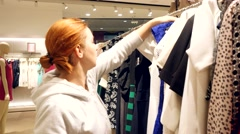 Pretty red-haired woman shopping in clothes store Arkistovideo