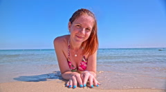 Woman lie down on beach sand smile in camera Stock Footage