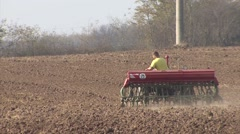 Farmer in tractor sows wheat Stock Footage