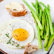 Green asparagus,fried egg and bread with butter. Stock Photos