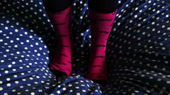 Two feets with cool socks that jumping and having fun on bed Stock Footage