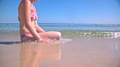 Waves splashing in to person sit on sand beach Stock Footage