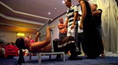 Man lean on sharp blade on stunt guy stomach Stock Footage