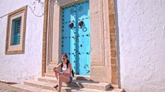Female tourist eating lunch in front of blue doors Stock Footage