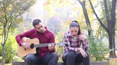 Man playing guitar while woman singing Stock Footage