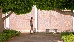 Woman walk around park and admire mosaic wall Stock Footage