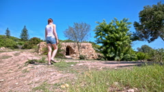 Female person walking towards ancient Carthage building Stock Footage