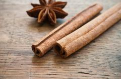 Dried anise and cinnamon on wooden background - stock photo