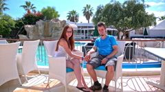 Couple sit at cafe with pool in background Stock Footage