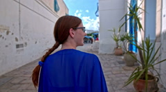 Woman walk through streets of Sidi Bou Said Stock Footage