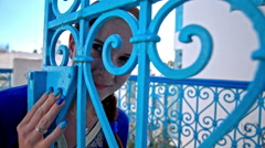 Attractive woman with blue fingernails behind the iron door Stock Footage