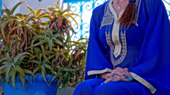 Person in Arabic traditional Sidi Bou Said dress sitting Stock Footage