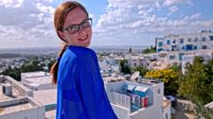 Woman in Sidi Bou Said Arabic dress posing on top of village Stock Footage