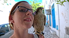 Woman portrait with saker falcon on shoulder Stock Footage
