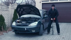 The man ridiculously inflates car wheels Stock Footage