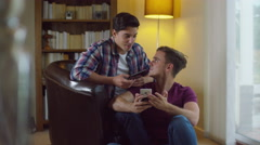 4K Attractive young gay couple relaxing at home, talking and using technology Stock Footage