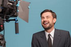 Attractive male tv journalist is reporting with joy - stock photo