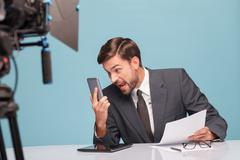 Professional male newscaster is foaming at the mouth - stock photo