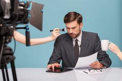 Cheerful male reporter before telling some news - stock photo