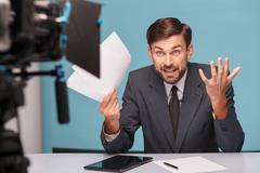 Attractive male reporter is expressing shock and indignation Stock Photos