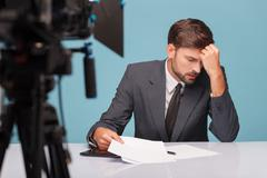 Handsome male newscaster is suffering from headache - stock photo