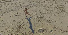 Little boy running on beach aerial footage Stock Footage