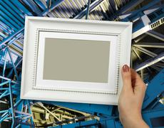 Wooden frame in woman hands. Abstract Metal construction background - stock photo