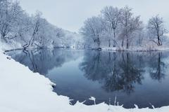 Winter landscape with river in forest - stock photo